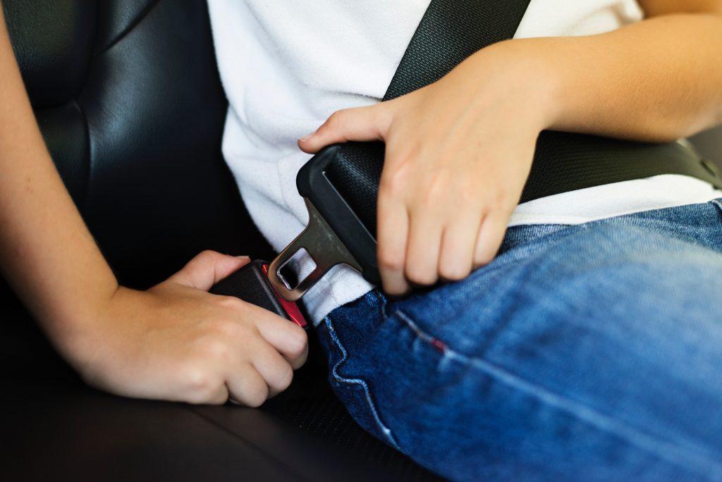 niño usando un cinturón de seguridad